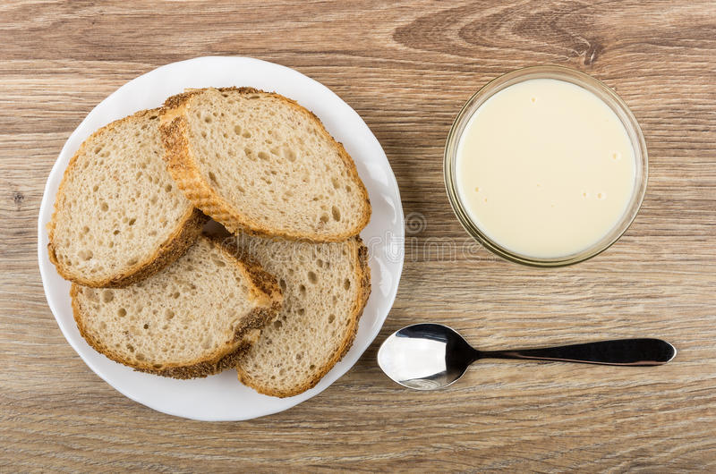 Partes de pão do trigo mourisco na placa, bacia com leite condensado fotografia de stock