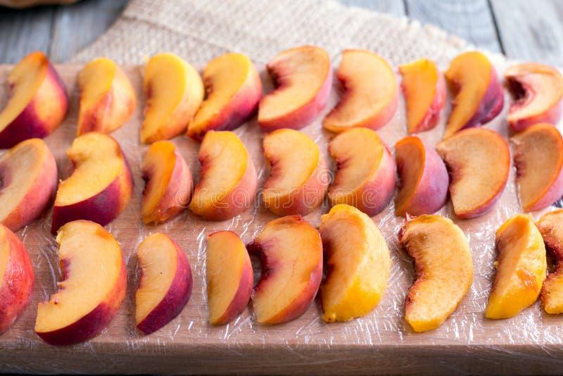 Partes de pêssegos em uma placa de corte para congelar-se fotos de stock royalty free