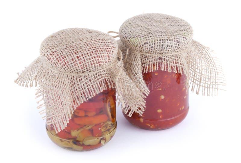 Partes de pimenta de pimentão vermelha e verde com molho do óleo e de pimentão nos bancos de vidro com a tampa do pano de saco em fotos de stock royalty free