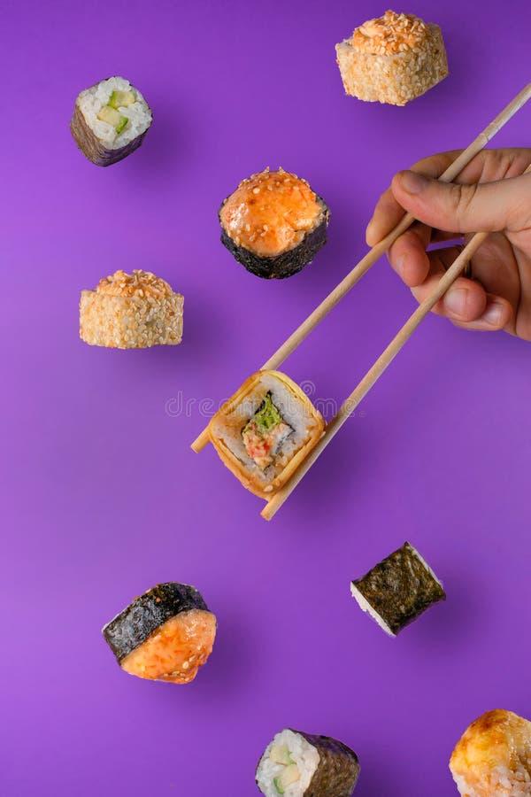 Partes de queda de sushi e de rolo de sushi com os hashis de madeira na mão masculina imagens de stock royalty free