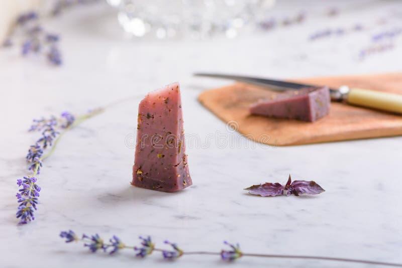 Partes de queijo da alfazema e de flores da alfazema em um worktop de mármore branco foto de stock