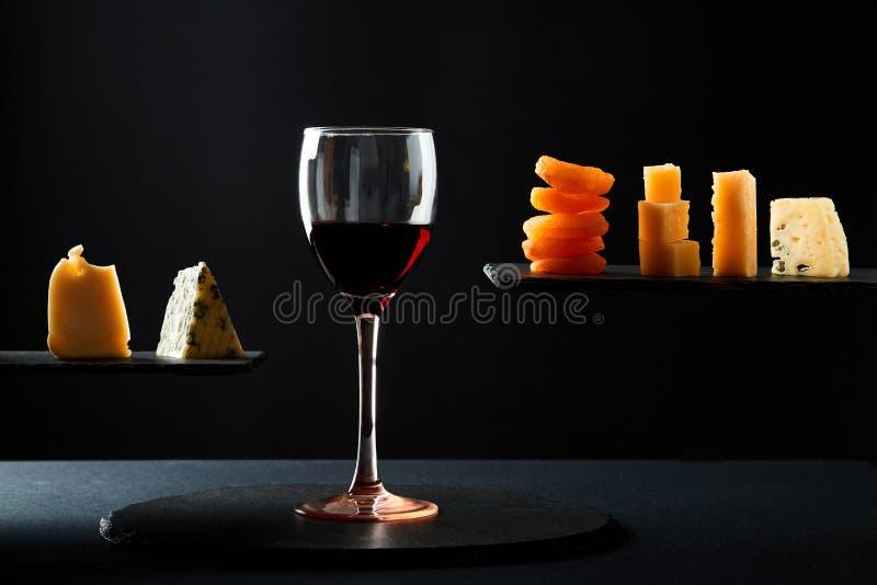 Partes de queijo e de frutos secos ao lado do vidro do vinho doce vermelho no fundo preto imagem de stock royalty free