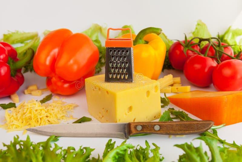 Partes de queijos, de queijo raspado, de grelha do metal, de faca, de tomates, de pimentas e de folhas dos frillis e da rúcula fotografia de stock