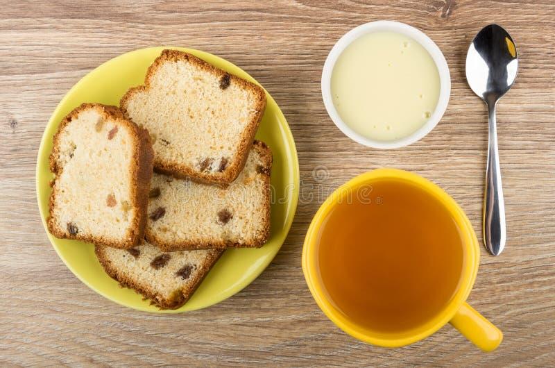Partes de queque nos pires, bacia com leite condensado, chá foto de stock