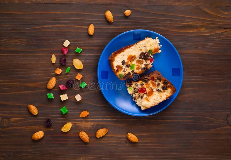 Partes de queques caseiros com passas, frutos cristalizados e amêndoas em uma placa azul em um fundo de madeira fotografia de stock royalty free