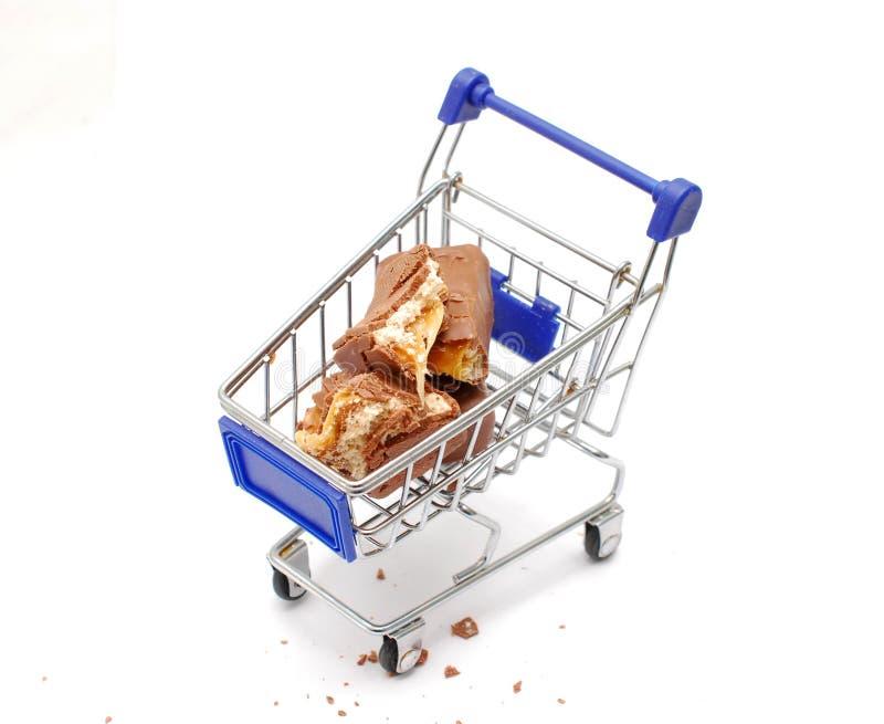 Partes de um chocolate e de uma barra de energia das porcas em um carrinho de compras pequeno imagem de stock royalty free