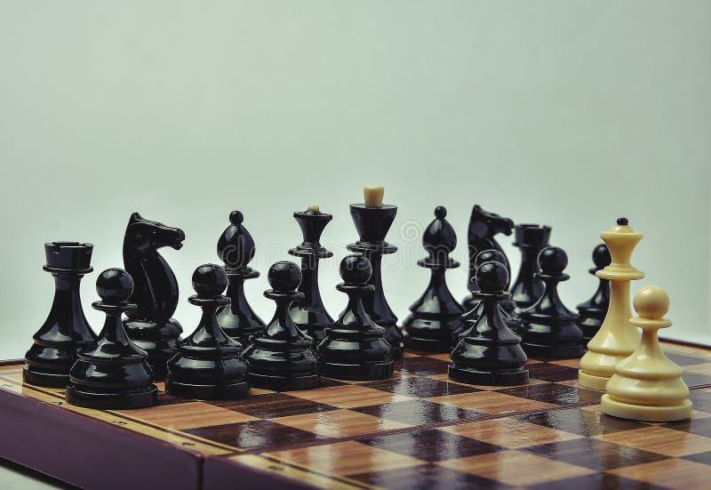 Partes de xadrez brancas e pretas em um fundo claro imagens de stock