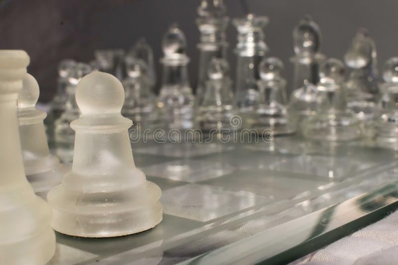 Partes de xadrez de vidro arranjadas em uma placa de xadrez de vidro fotografia de stock royalty free