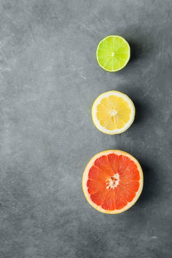 Partes del corte en media cal orgánica del limón del pomelo de los agrios en fondo de piedra oscuro Imitación de las luces de la  foto de archivo libre de regalías
