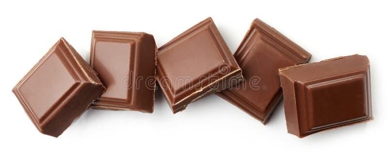 Partes do chocolate de leite no fundo branco imagem de stock royalty free