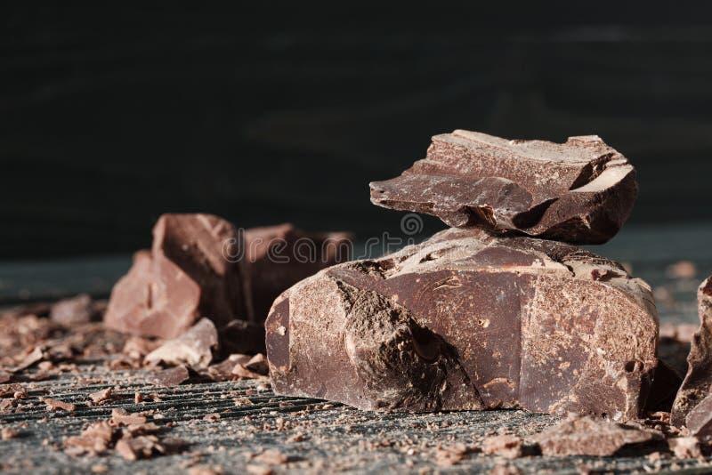 Partes do chocolate em um backround escuro foto de stock royalty free