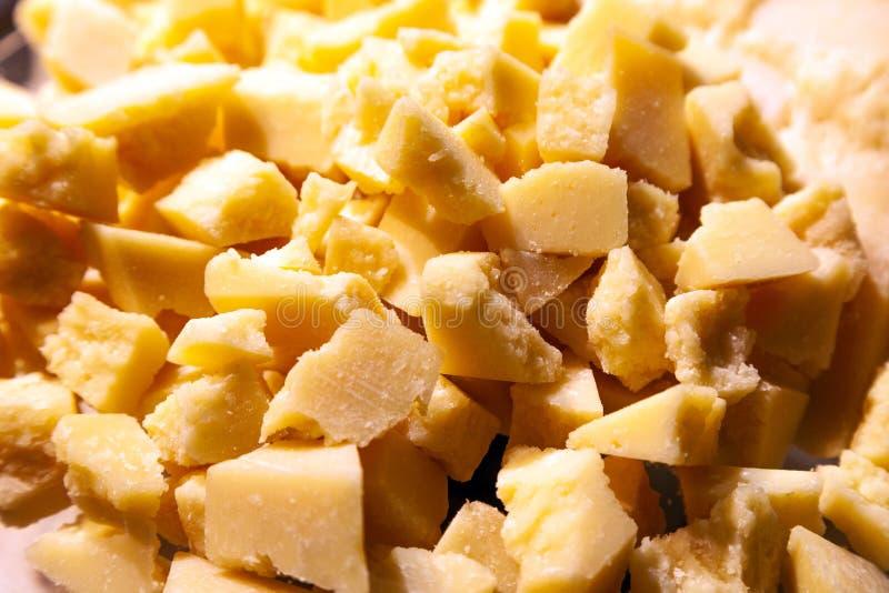 Partes do close up de Parmesão italiano quebrado esmagado do queijo duro Fábrica de queijo da excursão do conceito foto de stock royalty free