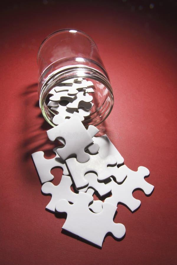 Partes do enigma de serra de vaivém que derramam o frasco de vidro fotografia de stock