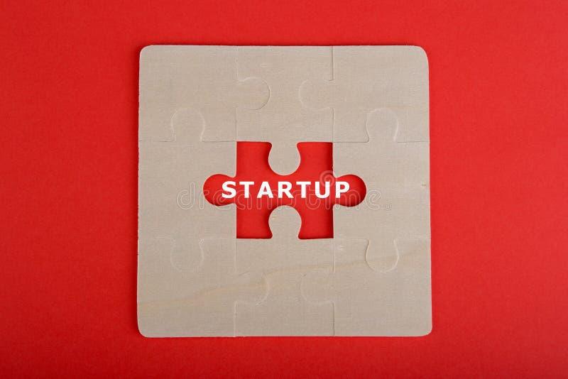 Partes do enigma de serra de vaivém com palavra & x22; Startup& x22; no fundo vermelho imagem de stock