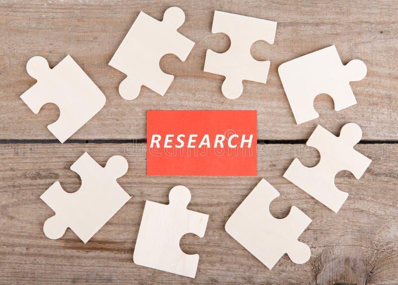 Partes do enigma de serra de vaivém com texto & x22; Research& x22; no fundo de madeira imagem de stock