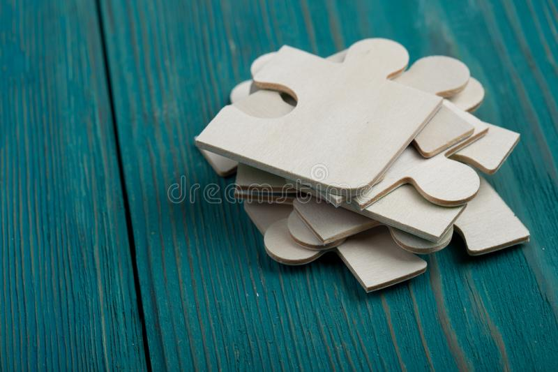 Partes do enigma no fundo de madeira azul imagem de stock