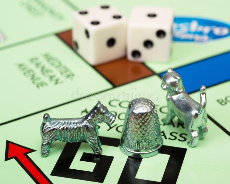 Partes do jogo e da placa do monopólio fotografia de stock royalty free