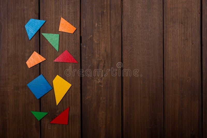Partes do jogo lógico de madeira na tabela marrom de madeira Copie o espaço fotos de stock