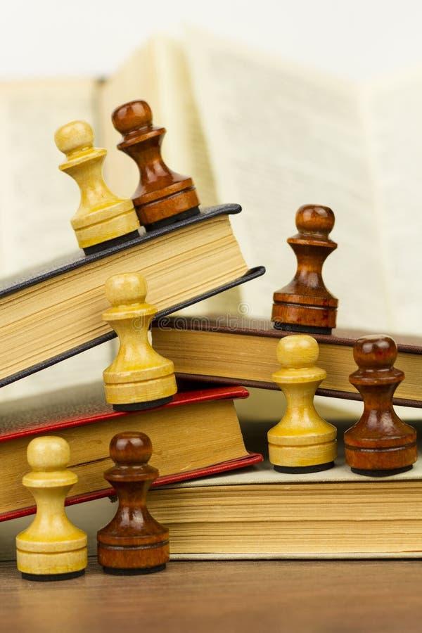 Partes e livros de xadrez em uma tabela de madeira foto de stock royalty free