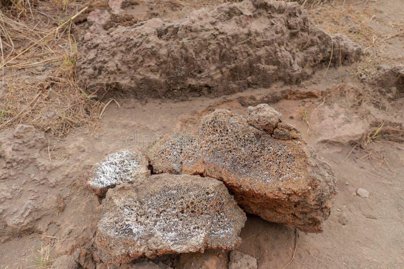 Partes endurecidas de pedras da lava Estrutura porosa da lava ígnea Pedras quebradas da lava no fundo arenoso e empoeirado sobre  fotografia de stock royalty free
