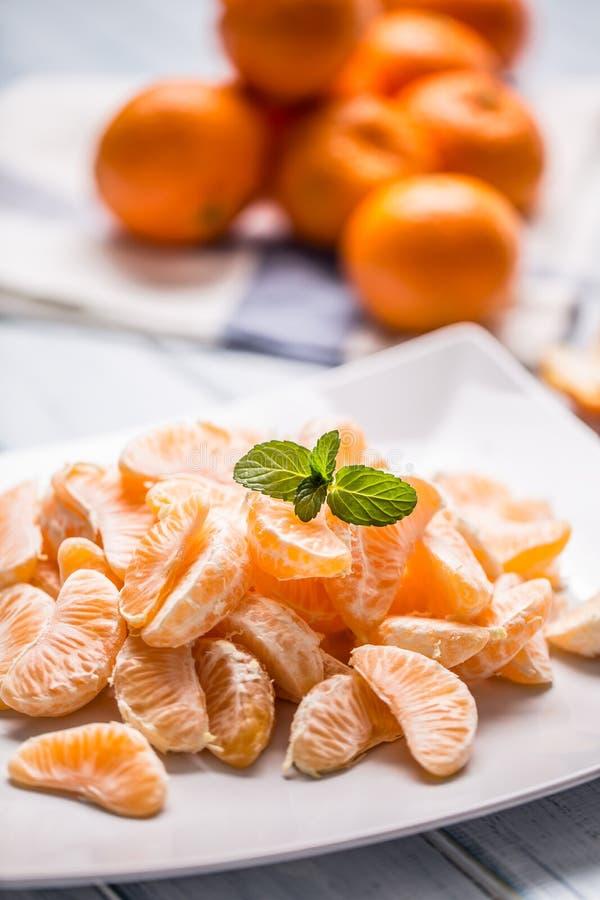 Partes frescas do mandarino das tangerinas na placa ou em uma bacia foto de stock