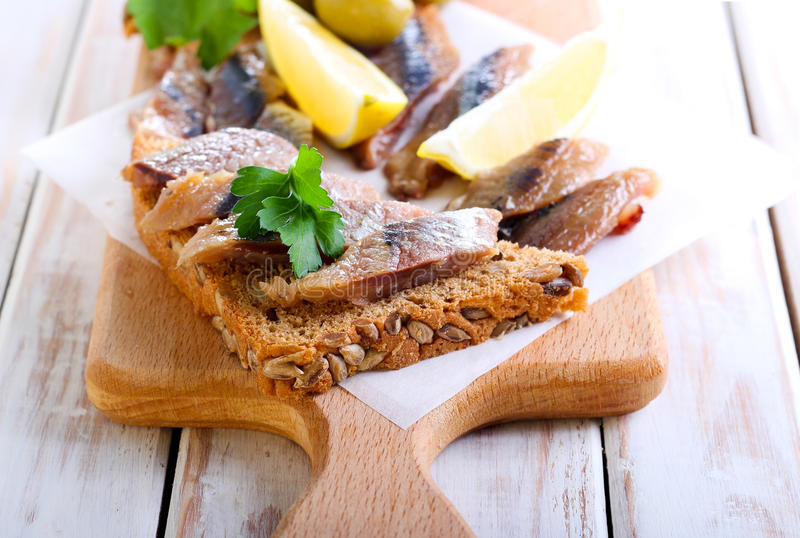 Partes fumado dos peixes no pão marrom da semente fotografia de stock royalty free
