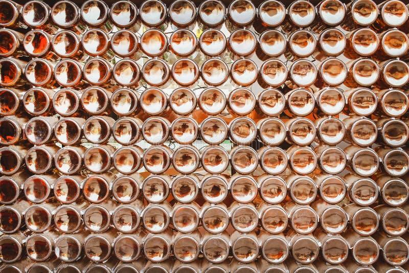 Partes inferiores de la textura marrón de los modelos del grupo de las botellas de cerveza en el extracto de la pared para el fon fotos de archivo libres de regalías