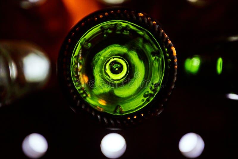 Partes inferiores verdes de las botellas de vino iluminadas por la luz brillante fotografía de archivo