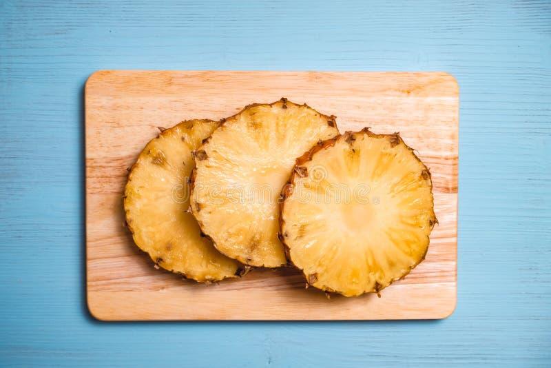 Partes maduras do abacaxi a bordo e tabela de madeira azul fotos de stock