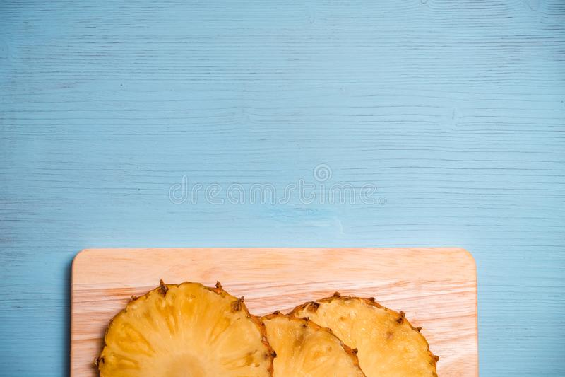 Partes maduras do abacaxi a bordo e tabela de madeira azul imagem de stock royalty free