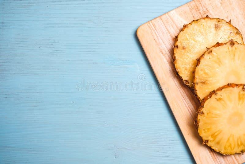 Partes maduras do abacaxi a bordo e tabela de madeira azul foto de stock