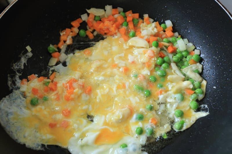 Partes pequenas da cebola branca, do alho, da cenoura, de ervilhas verdes e de ovo na bandeja de óleo fervida em processo do cozi fotografia de stock royalty free