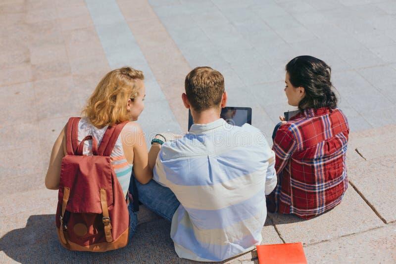 Partes posteriores de los estudiantes que se sientan en pasos fotos de archivo