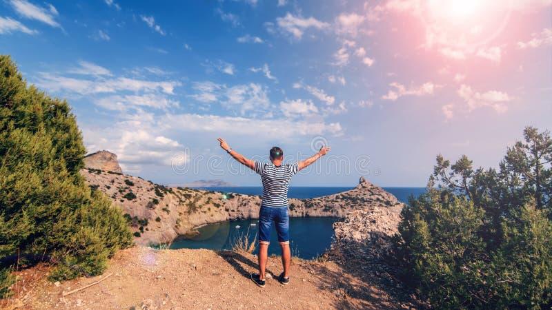 Partes posteriores del viajero del hombre encima de las montañas con sus manos para arriba contra el mar y el cielo soleado en ve imagen de archivo