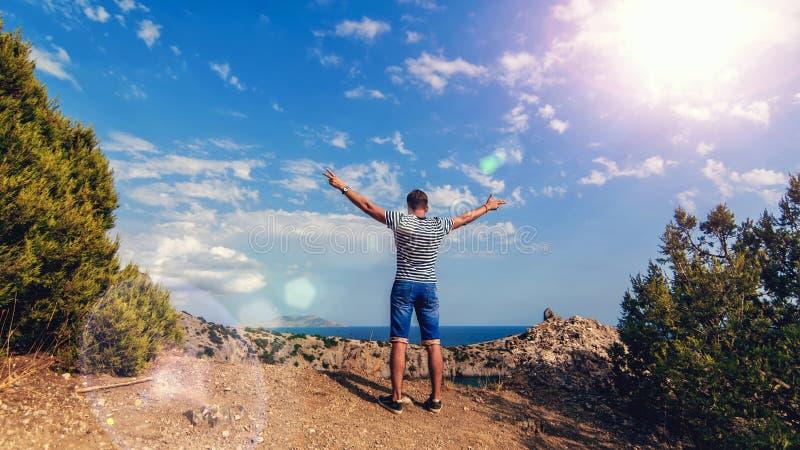 Partes posteriores del viajero del hombre encima de las montañas con sus manos para arriba contra el mar y el cielo soleado en ve fotos de archivo