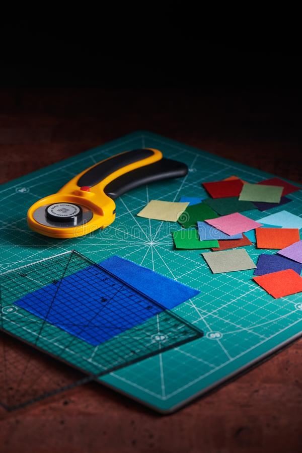 Partes quadradas do montão de telas coloridas, de cortador giratório e de régua em cortar a esteira imagens de stock