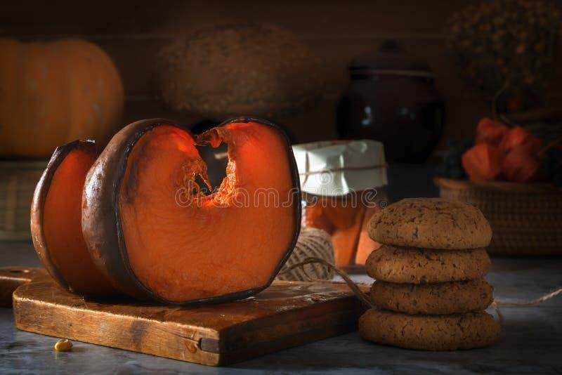 Partes recentemente cozidas de abóbora e de aveia em uma tabela rústica na perspectiva dos utensílios da cozinha e de uma cesta c fotografia de stock
