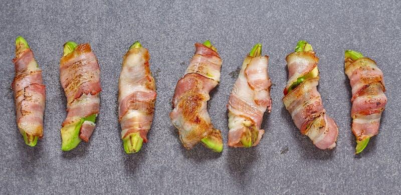 Partes Roasted do abacate envolvidas no bacon fotos de stock royalty free
