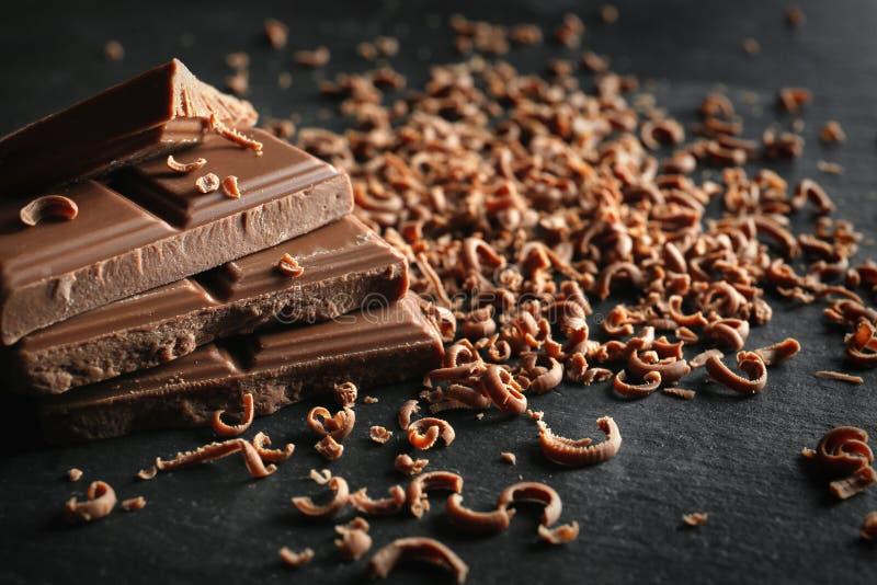 Partes saborosos e aparas do chocolate de leite na tabela escura imagem de stock