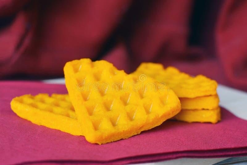 Partes saudáveis triangulares amarelas do waffle da abóbora no fundo roxo escuro imagens de stock royalty free