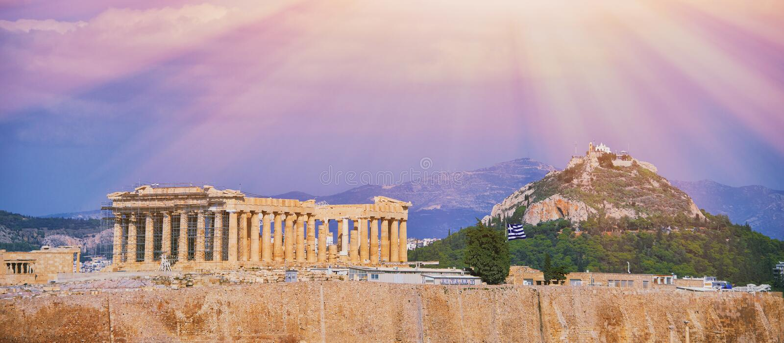 Parthenon temple in Acropolis Hill in Athens, Greece shot in sunny day afternoon with clouds in blue sky over the old town during royalty free stock photo