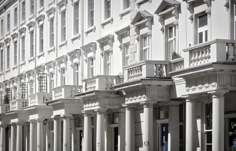 Parti anteriori bianche della casa con le colonne ed i balconi fotografia stock