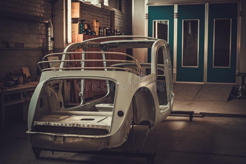 Parti classiche del bodykit dell'automobile nell'officina della pittura immagine stock