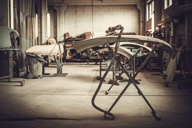 Parti classiche del bodykit dell'automobile nell'officina della pittura fotografie stock libere da diritti