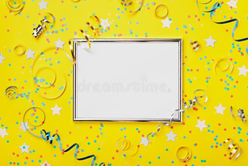 Parti, dekorerad silverram för karneval eller för födelsedag bakgrund med färgrika konfettier och banderoll på gul bästa sikt för royaltyfria bilder