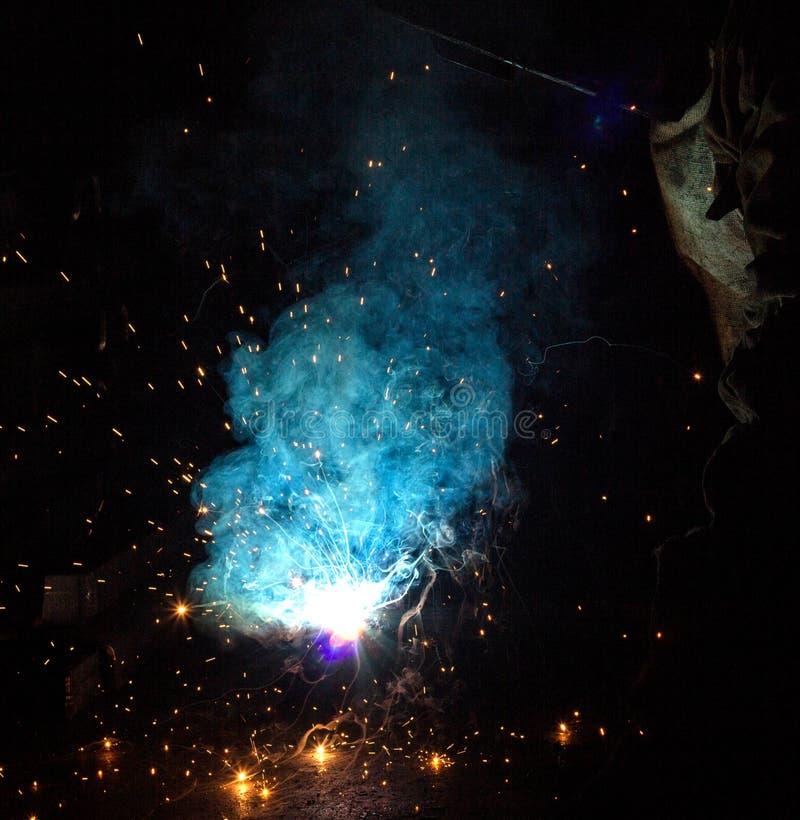 Parti di metallo delle saldature del saldatore, molte scintille e vapori, saldatura, arco di saldatura, flash luminoso, primo pia immagine stock