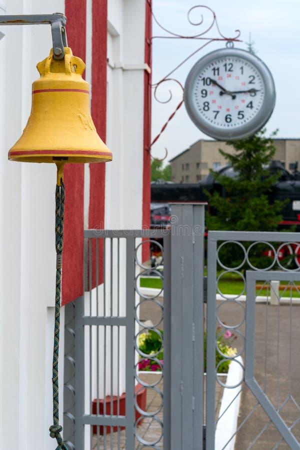 Parti di vecchia stazione ferroviaria Retro orologio e campana sul binario del treno fotografia stock libera da diritti