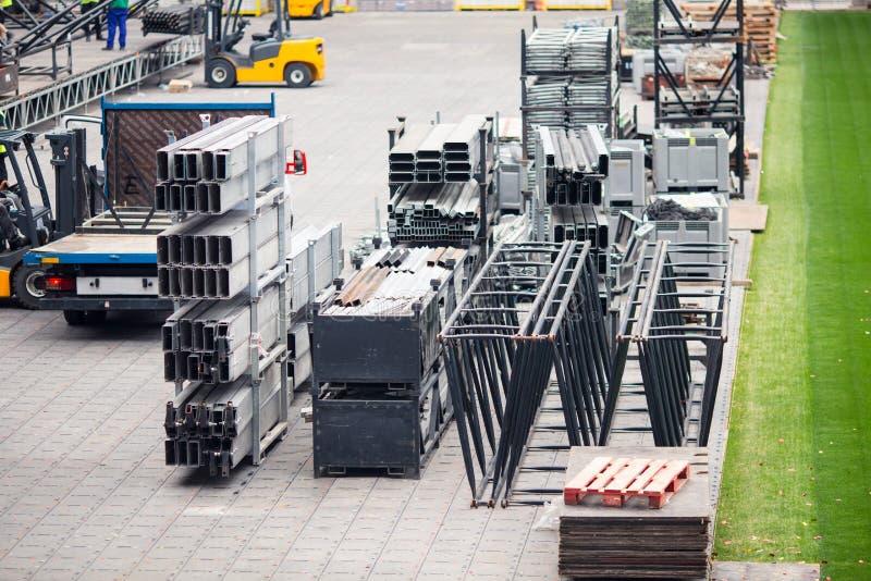 Parti differenti dell'impalcatura del metallo sul campo di costruzione I lavoratori sviluppano una fase di concerto fotografie stock