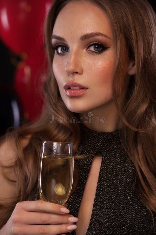 Parti drinkar, ferier, berömbegrepp - kvinna i aftonklänning med exponeringsglas av mousserande vin på ballonsbakgrund arkivbild