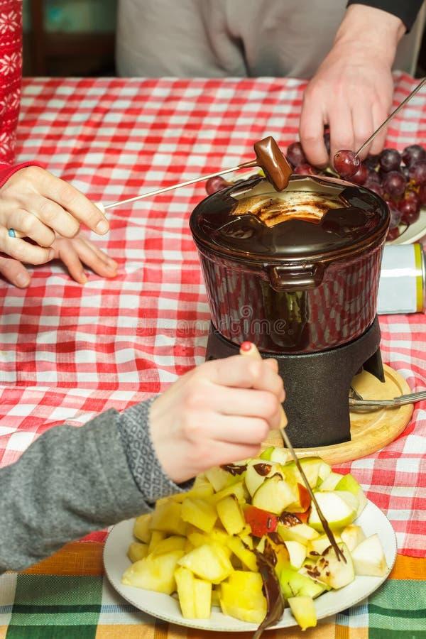 Parti för fondue för söt choklad för efterrätt med kuber av äpplen, päron, ananors och druvor arkivfoto